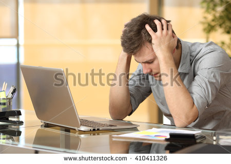 stock-photo-worried-businessman-lamenting-in-front-of-a-computer-after-a-big-mistake-at-office-410411326